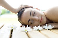 Woman lying on deck having head massage, surrounded by flowers