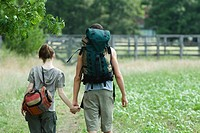 Young couple going for hike, rear view