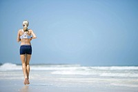 Young woman running on beach, rear view