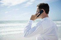 Young man using cell phone on beach, side view