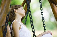 Young woman sitting on swing, looking away, side view