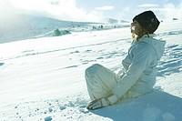 Teen girl sitting on snow