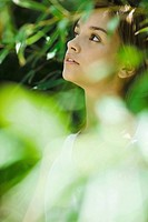 Young woman standing in thick foliage, looking away