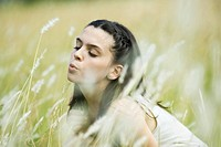 Teen girl in field, blowing tall grass