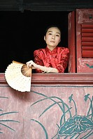 Young woman dressed in traditional Chinese clothing, leaning out of window sill, holding fan