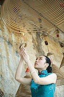 Young woman dressed in traditional Chinese clothing lighting spiral incense hanging from ceiling, low angle view