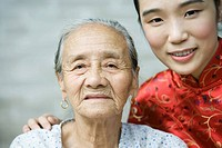 Young woman wearing traditional Chinese clothing posing with elderly grandmother, portrait