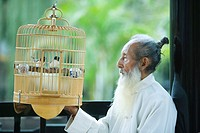 Elderly man in traditional Chinese clothing, looking at birds in bird cage