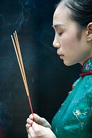 Young woman dressed in traditional Chinese clothing holding sticks of incense, eyes closed