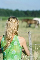 Young woman standing by fence in rural field, rear view