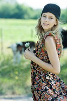 Young woman standing with flower in hand in rural setting, smiling at camera