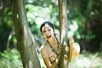 Young woman standing behind tree, smiling at camera