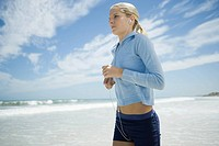 Young woman jogging on beach, listening to MP3 player