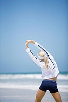 Young woman in active wear stretching on beach, rear view