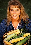 A young farm woman holds a basket of sweet corn on a farm / Jefferson County, Wisconsin, USA MR