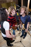 Guitarists singing into microphone in recording studio