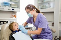 Female dentist examining boy