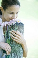 Woman leaning on wooden post, smelling flowers