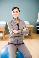 Asian woman sitting on exercise ball