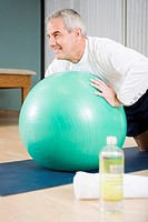 Senior man exercising on ball