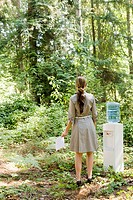 Businesswoman next to water cooler in woods