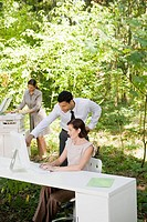 Businesspeople looking at computer in woods