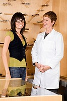 Female optician and woman in office