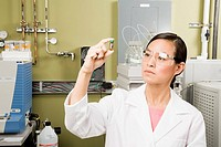 Asian female scientist examining vial