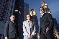 Portrait of two businessmen standing with a businesswoman with skyscrapers in the background, Singapore