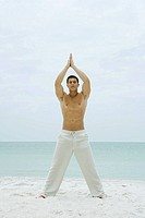Man standing on beach, doing yoga, full length