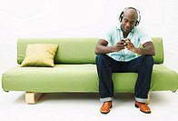 Young man sitting on sofa, wearing headphones and holding mp3 player