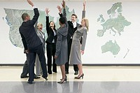 Business people standing in circle, cheering and raising hands, in office with world map on wall