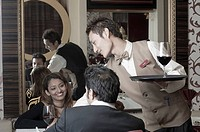 Waiter serving red wine to a young couple in a restaurant