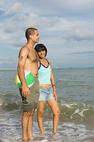 Young couple standing on the beach with a beach ball and smiling
