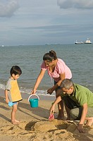 Mid adult couple making a sand castle on the beach with their son