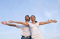 Low angle view of a young couple standing together with their arms outstretched and smiling