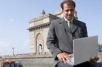 Businessman using a laptop with a monument in the background, Gateway of India, Mumbai, Maharashtra, India