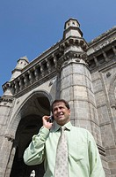 Low angle view of a businessman talking on a mobile phone and smiling, Gateway of India, Mumbai, Maharashtra, India