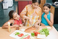 Close-up of a mid adult woman making sandwiches with her daughters