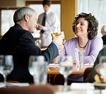 Mature couple sitting, toasting, in restaurant, waiter in background