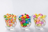 Row of three cups filled with jellybeans and candies