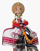 Portrait of a Kathakali dance performer sitting on a motorcycle