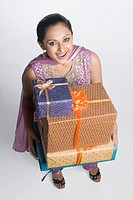 High angle view of a mid adult woman holding a stack of gift boxes