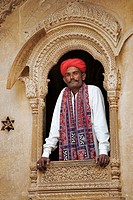 India, Jaisalmer, man leaning out of window of a haveli, portrait