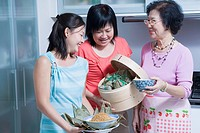 Senior woman with her daughter and granddaughter in a kitchen