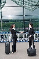 Two businesswomen shaking hands outside an airport