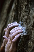 the chalked up hands of a determined climber hanging on to a ledge, Skaha, Penticton, British Columbia, Canada