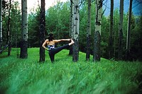 a young athletic woman doing yoga among the trees and mountains of Banff National Park, Alberta, Canada