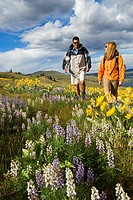 A young couple shares some conversation while hiking through spectacular spring wildflowers over Stump Lake, near Kamloops, British Columbia, Canada
