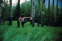 As young woman doing some yoga in the tall grass and forest in Banff National Park, Alberta, Canada